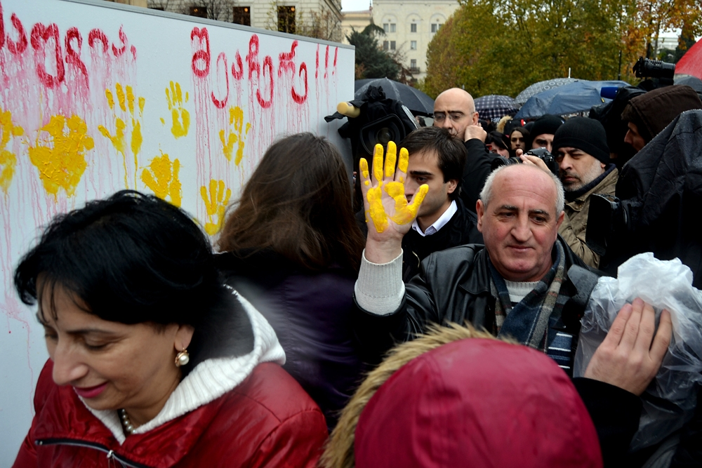 Activists in Tbilisi pressed their paint-coated hands against a board in support of domestic abuse victims. (Giorgi Lomsadze)