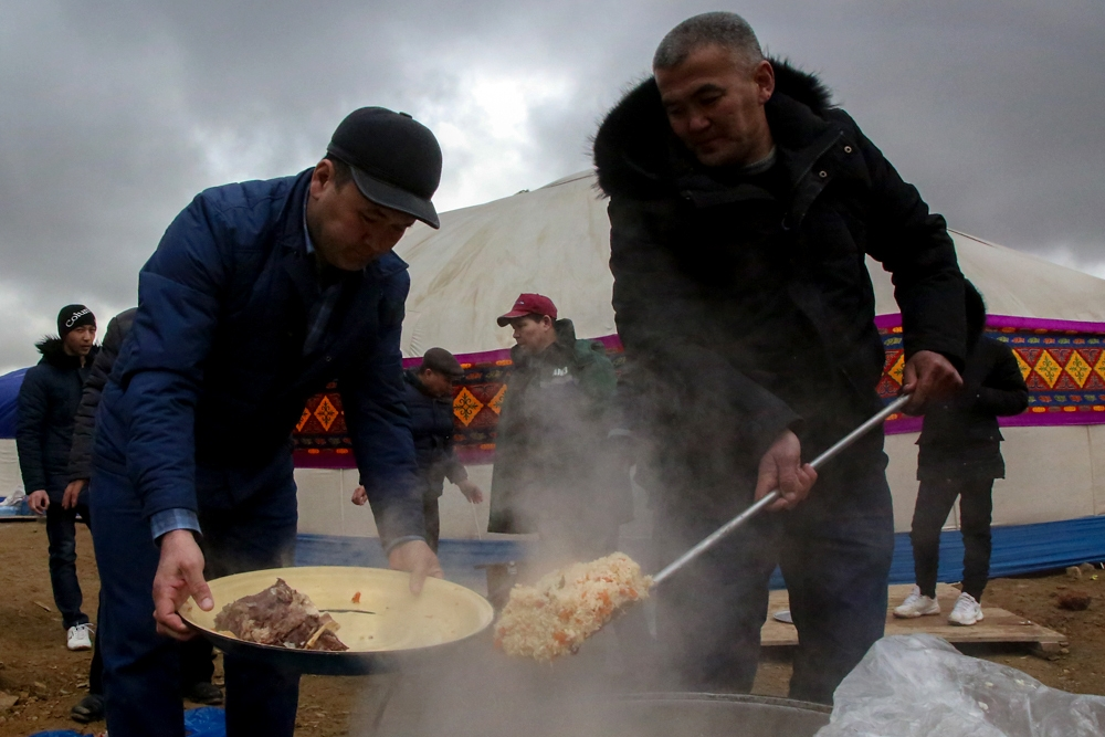 Men prepare platters of a Central Asian dish called plov.