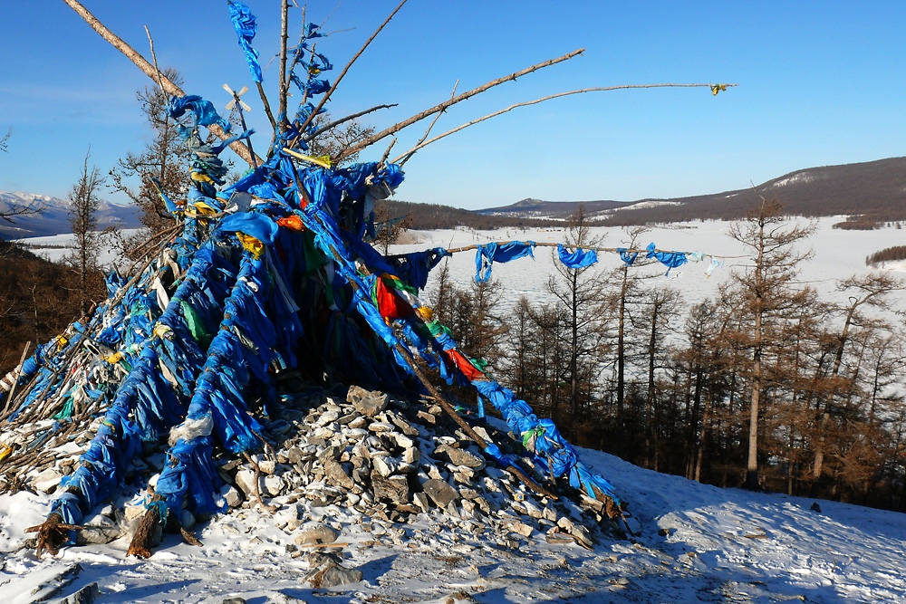 A shamanic ovoo, a kind of shrine, decorated with silk scarves sits on a hill overlooking frozen Khovsgol Lake.