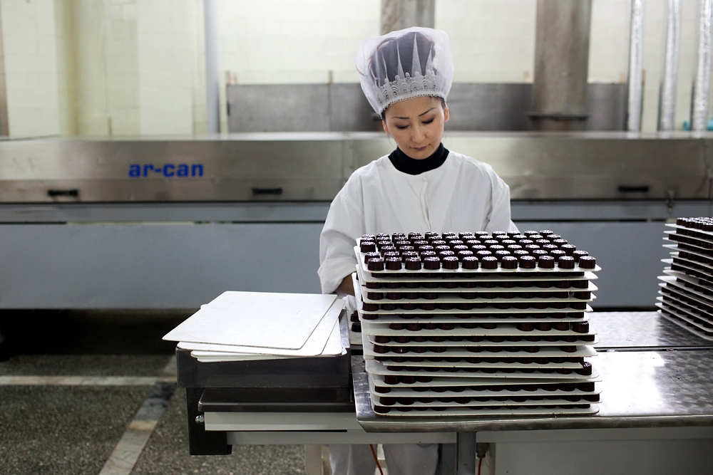 A woman sorts chocolates before feeding them into an automated wrapping machine.