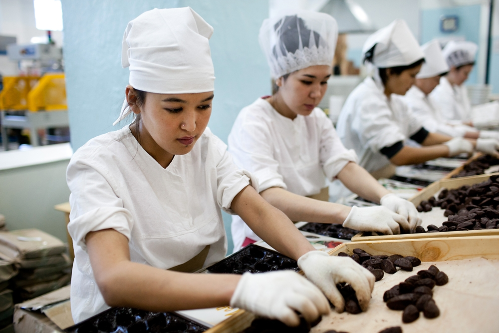 Workers sort chocolates on the packaging line.