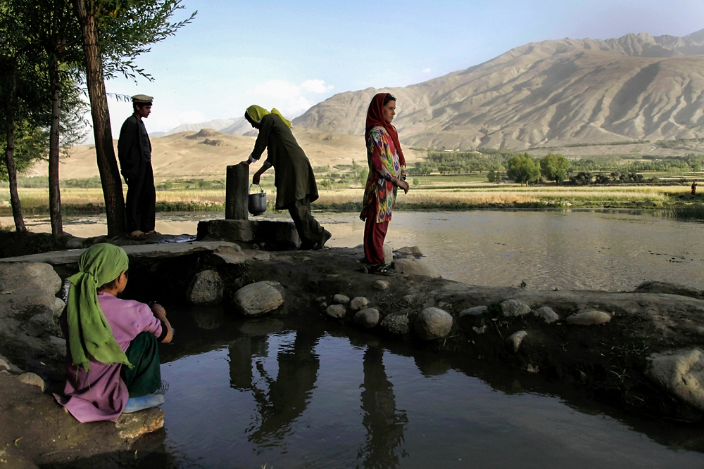Afghan woman gather water from a stream running through Ishkashim, Afghanistan.