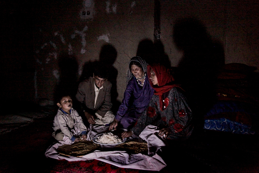 An Afghan family eats dinner in the dark in Ishkashim, where most of the region is without electricity.