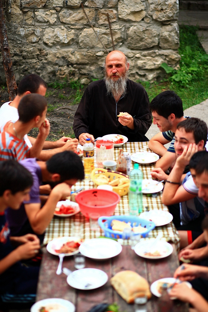 Father Maxim eats with some of the volunteer builders.
