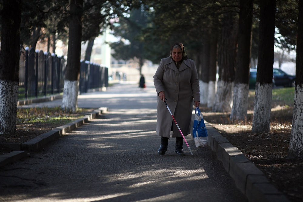 A resident of the settlement for the visually impaired walks home from the district's soup kitchen.