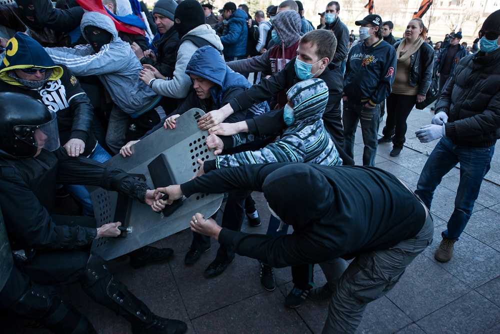 Pro-Russian demonstrators rip riot shields from the hands of Ukrainian police in Donetsk on April 6.