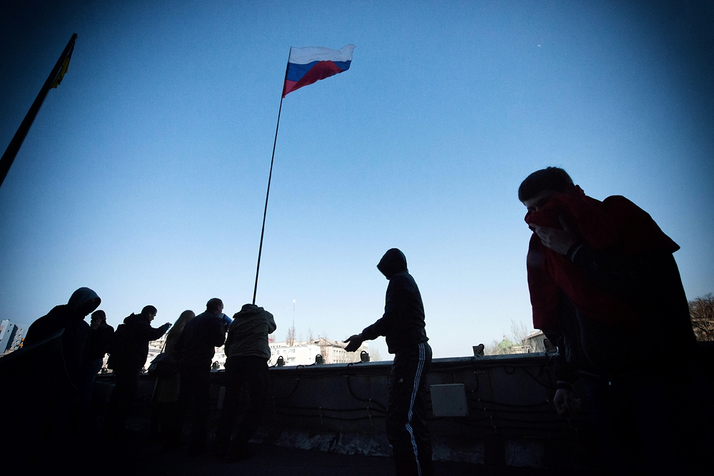 Several offices inside the building were vandalized before demonstrators hoisted a Russian flag on the roof of the building.