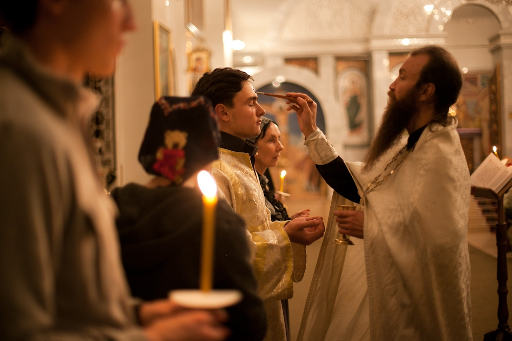A priest anoints an alter boy with holy oil at a smaller service the Wednesday before Easter.