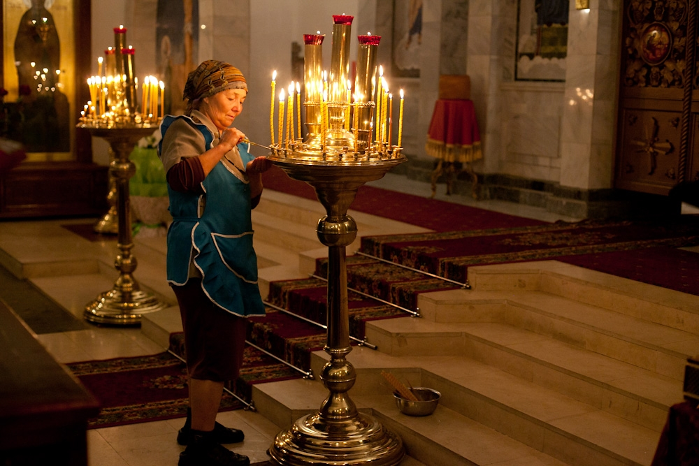 During the ceremony, a woman keeps the candleholders clean.