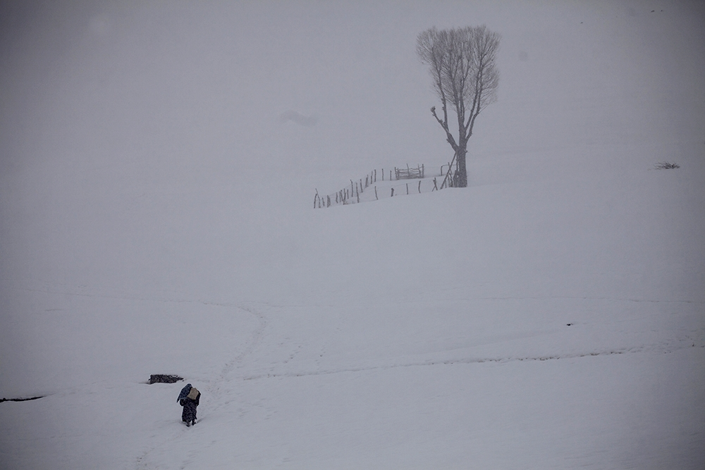 A villager climbs a hillside in deep snow in the village of Çengilli.