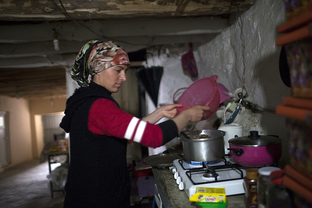 An Armenian girl, who does not speak Armenian, cooks at home in one of the villages of the Sason region.