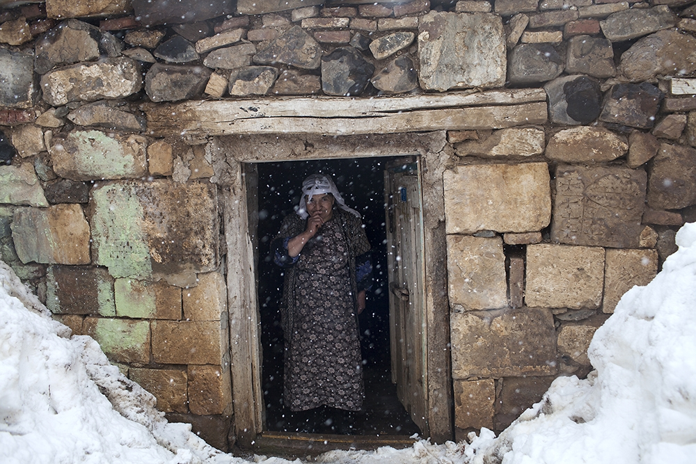 A woman stands in front of her tonir, used to bake bread, that was built using the stones of an Armenian church in Çengilli.