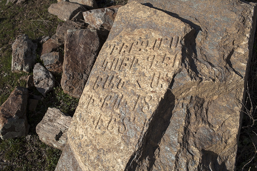 A broken gravestone shows weathered signs of old Armenian script in the city of Muş.