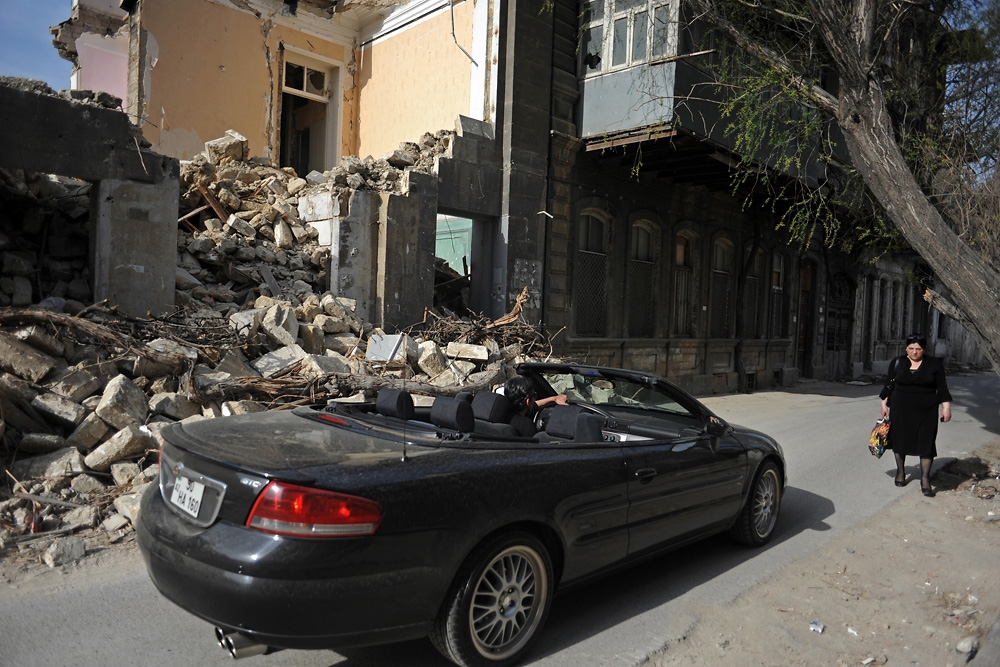 A man drives by in a convertible as a woman walks down the street beside a demolition site.
