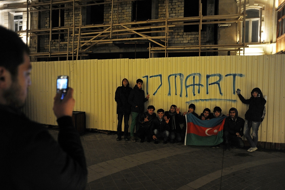 Near a construction site, young Azeris pose for a photo after holding a rally against the mass demolition work by the city.