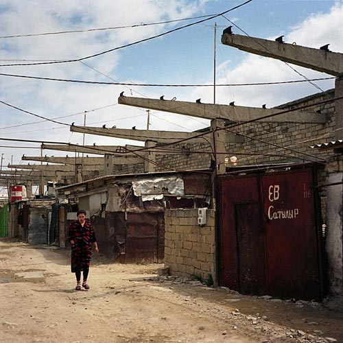 A woman walks along a dusty street in the shantytown near the closed compressor factory.