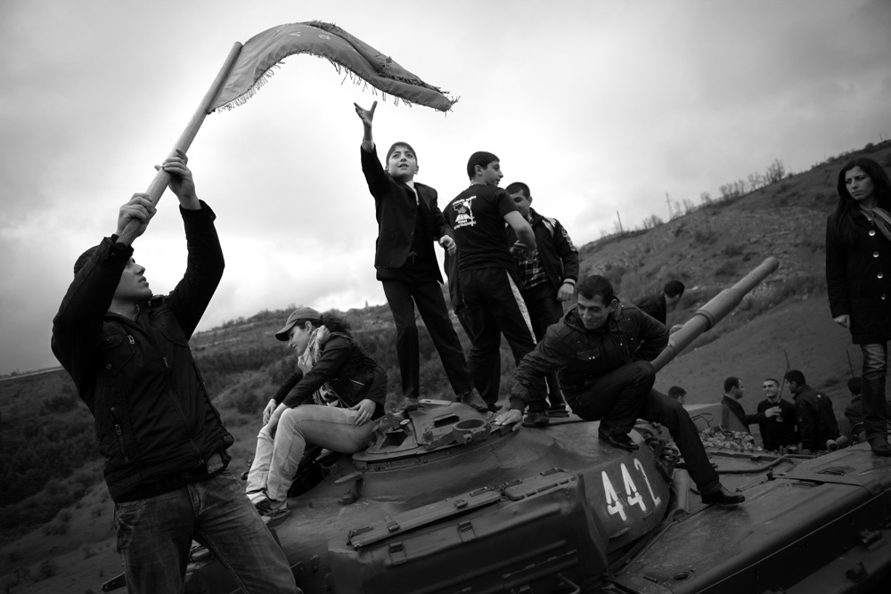 Teenagers celebrate an Armenian victory on a tank set up as a memorial near Shusha, called Shushi within Karabakh and Armenia.