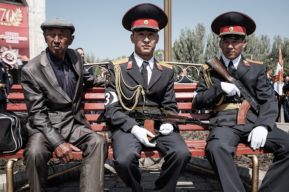 Kyrgyz officers relax with their weapons during a break in the parade rehearsal in Ala-Too Square.