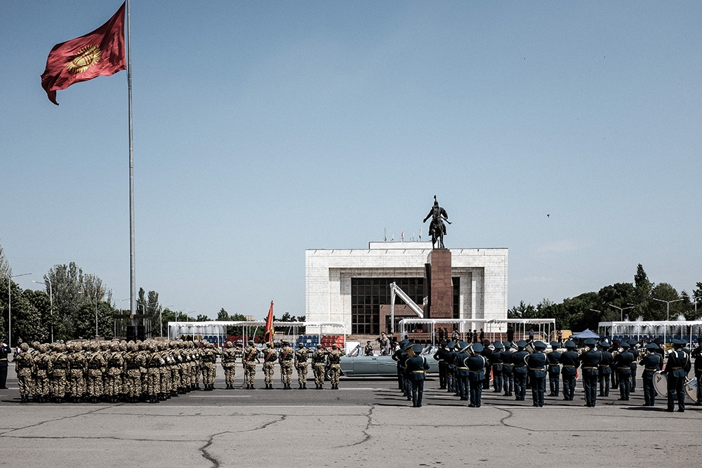 Kyrgyzstan's Chief of the General Staff Asanbek Alymkozhoev drives by to greet Kyrgyz troops (left) and Russian troops.