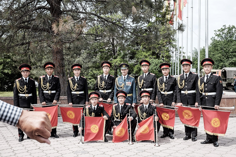 A Russian Air Force officer poses with Kyrgyz military band members at the end of the rehearsal.