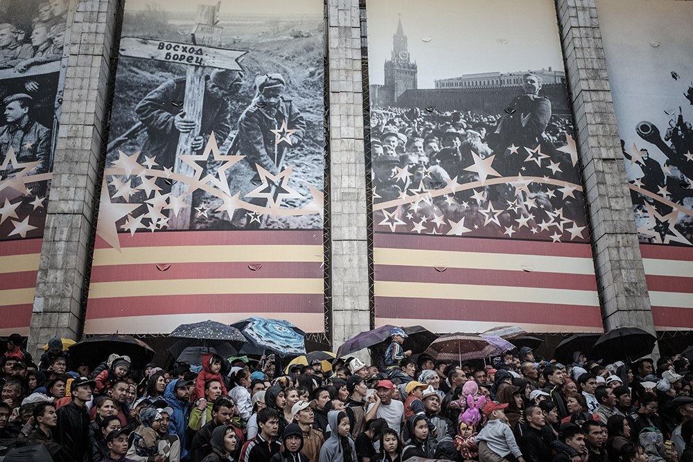 Under large photos of Soviet military scenes from World War II, spectators watch the parade.