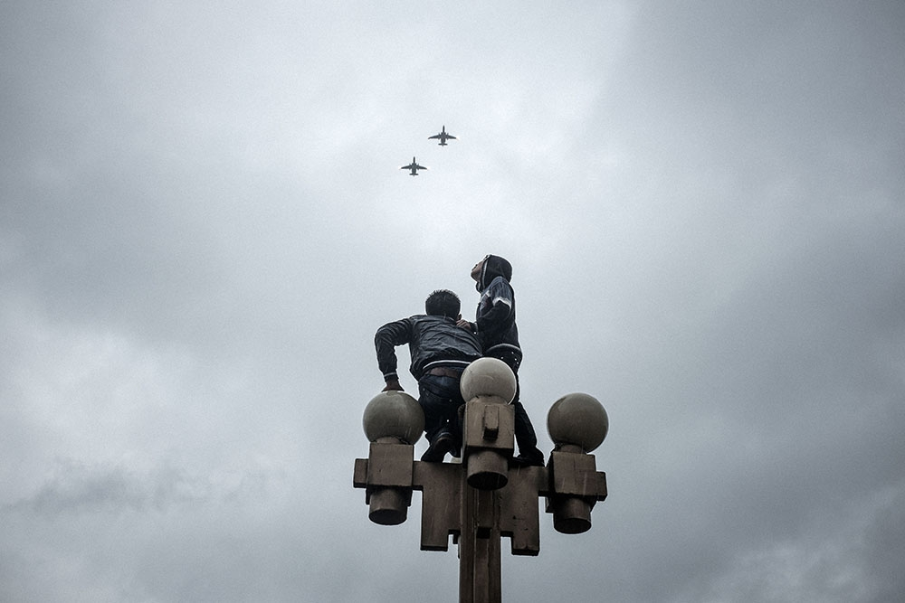 Perched on a lamp post in central Bishkek, spectators watch two jet fighters fly over the parade.