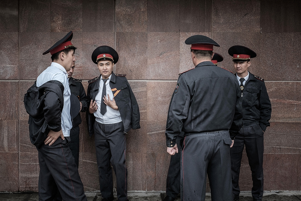 Kyrgyz police chat and relax at the end of the day of celebrations.