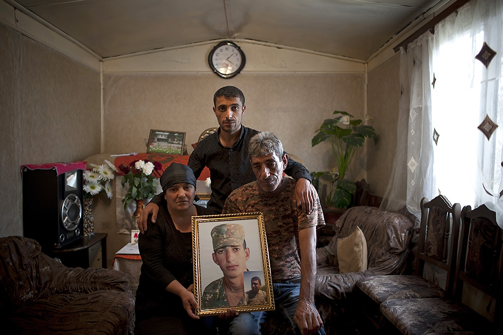 Kyaram Sloian's mother, father and brother hold his portrait at their home in the western Armenian region of Aragatsotn.