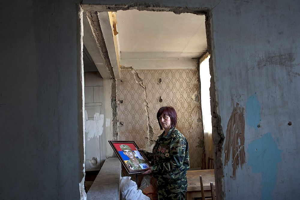 Anahit Harutyunian holds a portrait of her killed son, Grigor, at the home where they lived together.