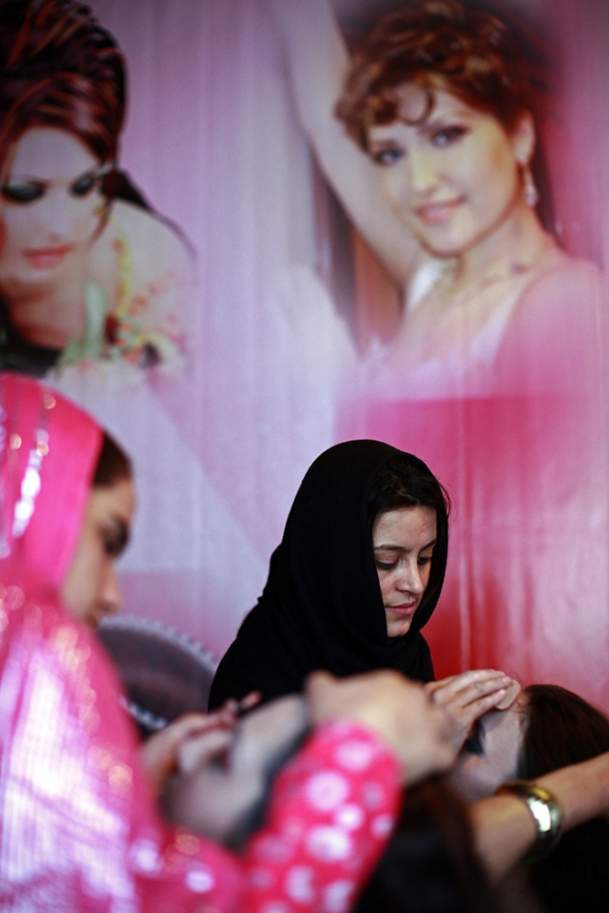 A backdrop of glamorous uncovered women printed on a pink curtain dominates the salon.