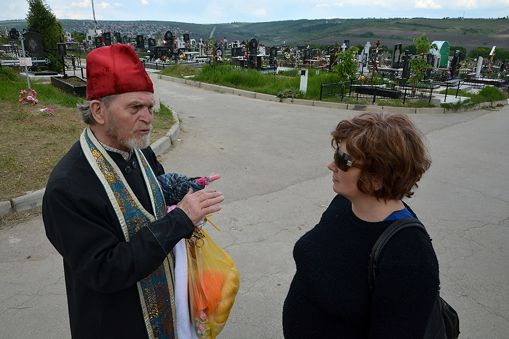 An Orthodox priest talks to a visitor at the cemetery, one of the largest in Europe at more than 207 hectares (164 acres).acr.