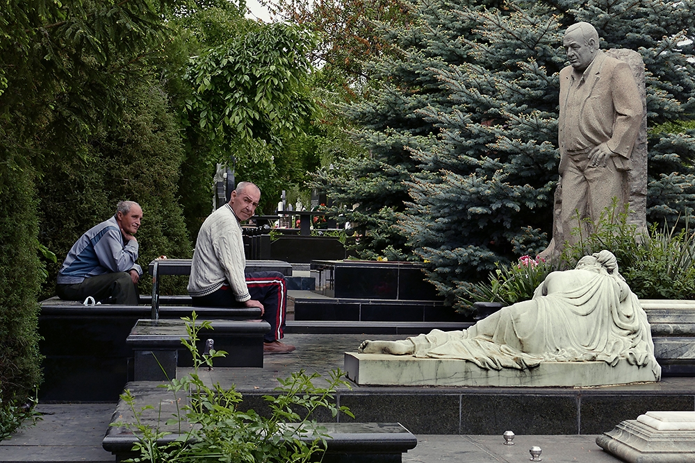 Visitors relax at the grave belonging to Valeriu Rotari, reputed as a gunned-down, high-ranking organized crime member.