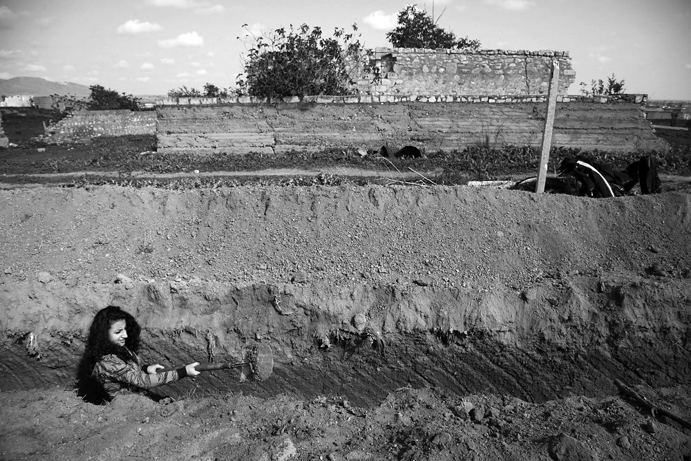 A female volunteer digs a new frontline trench for Nagorno Karabakhi soldiers.
