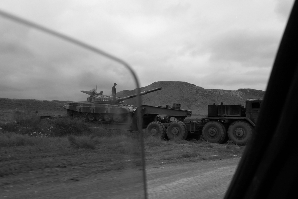 Tanks are loaded onto a carrier near the frontline with Azerbaijan.