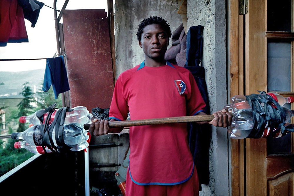 Datchoua Nemale Olivier uses makeshift weights made from plastic bottles filled with water to keep in shape.