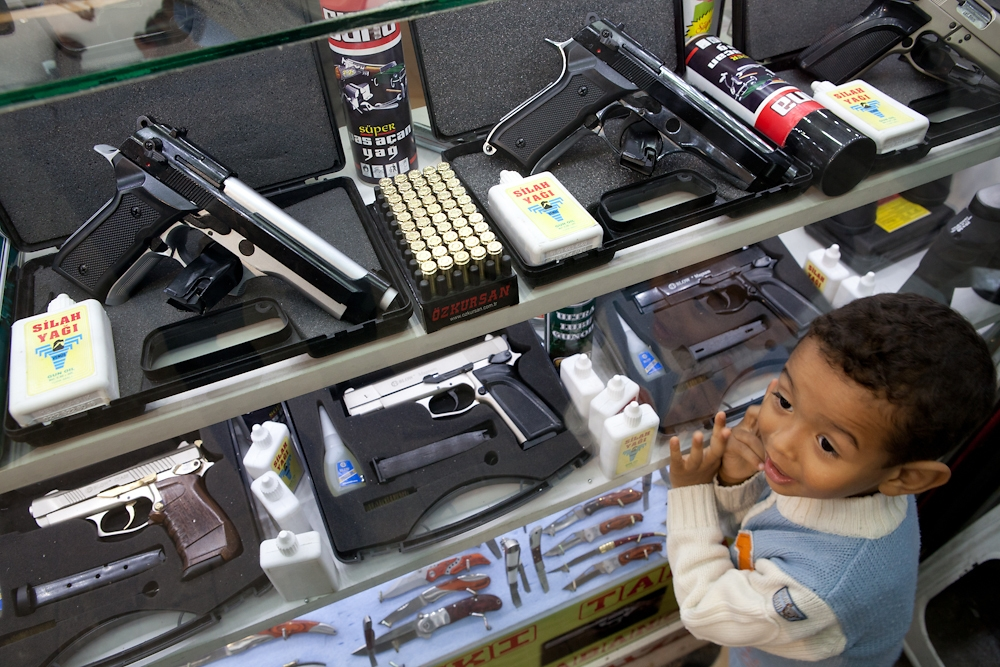 A boy plays next to a case displaying air guns and handguns that shoot blanks.
