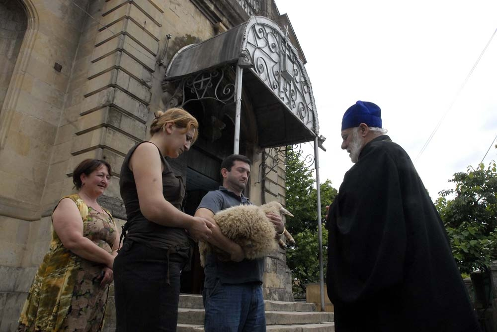 A family brings a lamb for sacrifice on Ninoba (St. Nino's Day) to a church in Kutaisi.