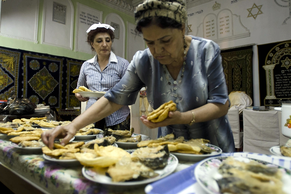 Women prepare plates of fried fish and bread during the dinner for Yuri's deceased mother.