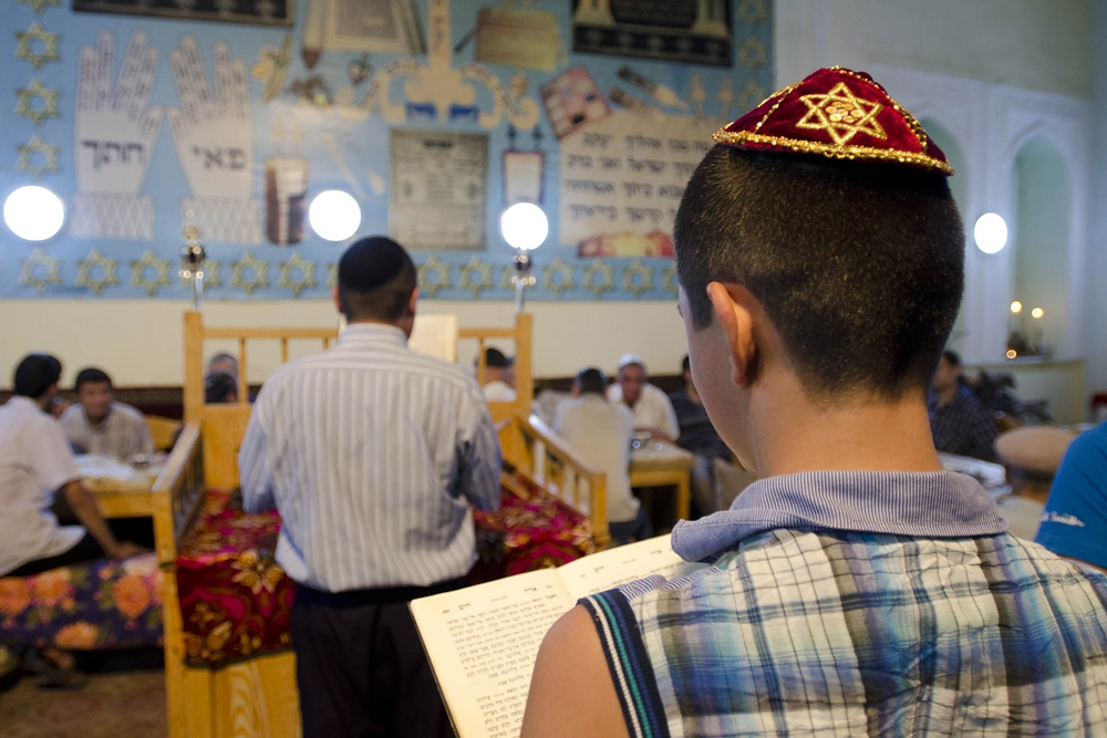 Eleven-year-old Iosef Olnatanov reads along from his Torah during the ceremony.