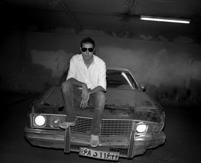 Behzad Eliasazar, a 24-year-old designer, sits on the hood of his '70s-era American-made Chevrolet in a garage in Tehran.