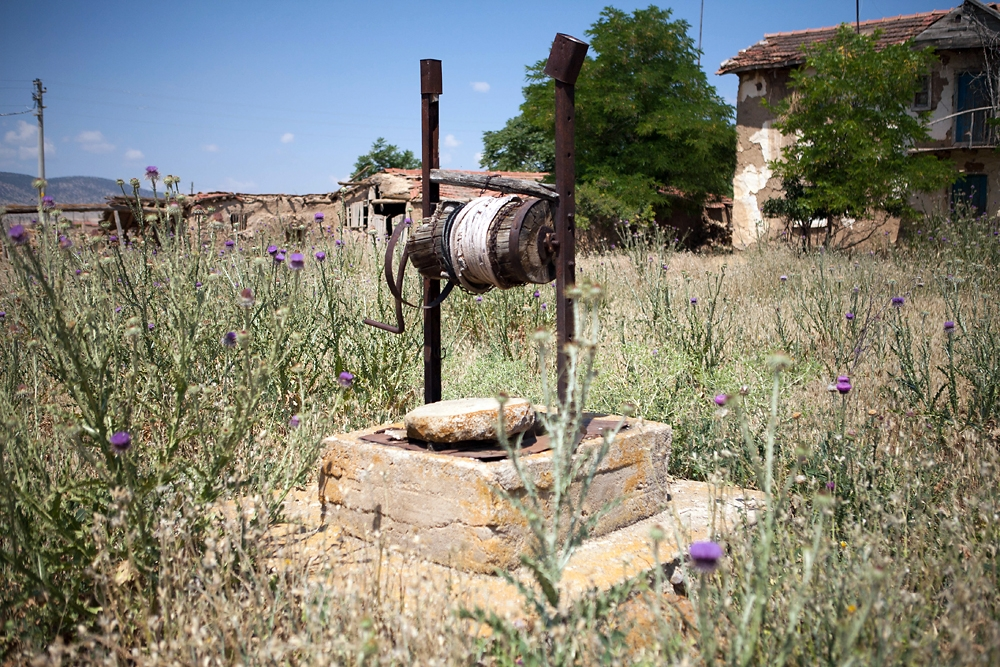 The first well in Osmaniye sits in a field of overgrown weeds, in front of abandoned houses.