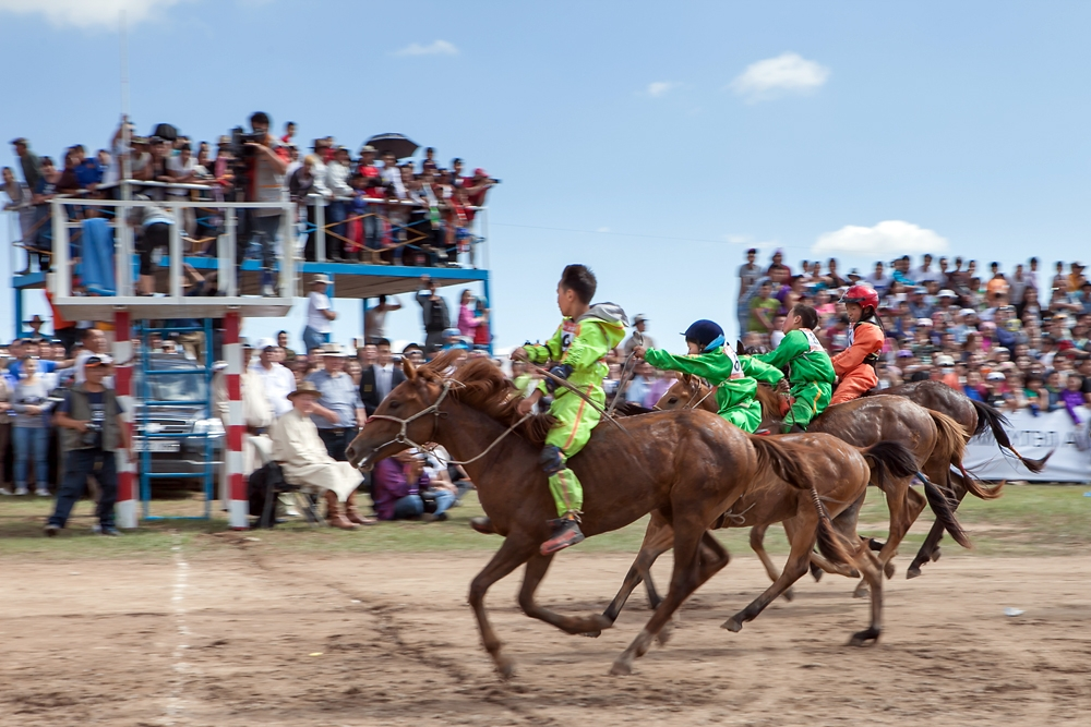 Four young riders race for the finish line in the 15-kilometer race for 2-year-old horses.