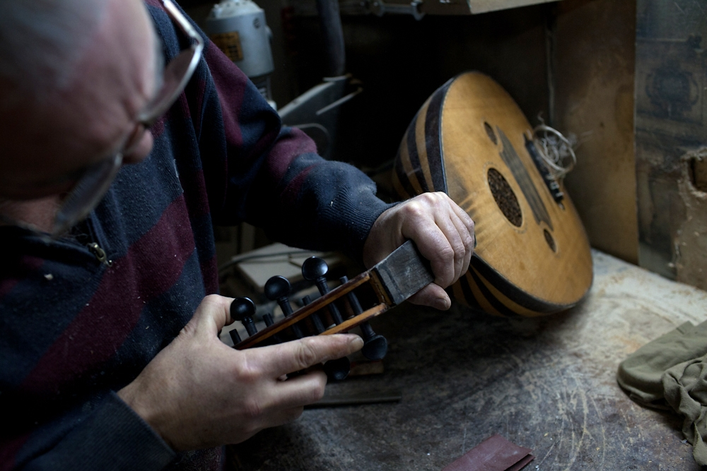 A local oud maker studies an older instrument so that he can undertake repairs.
