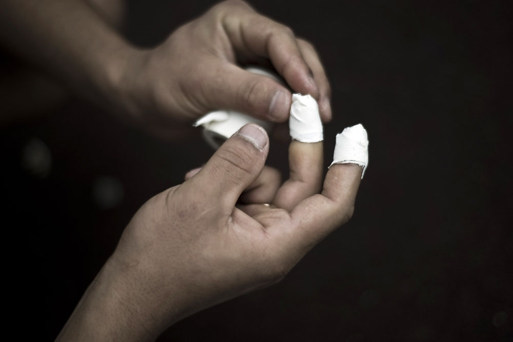 A player tapes up his finger tips before the start of his match.