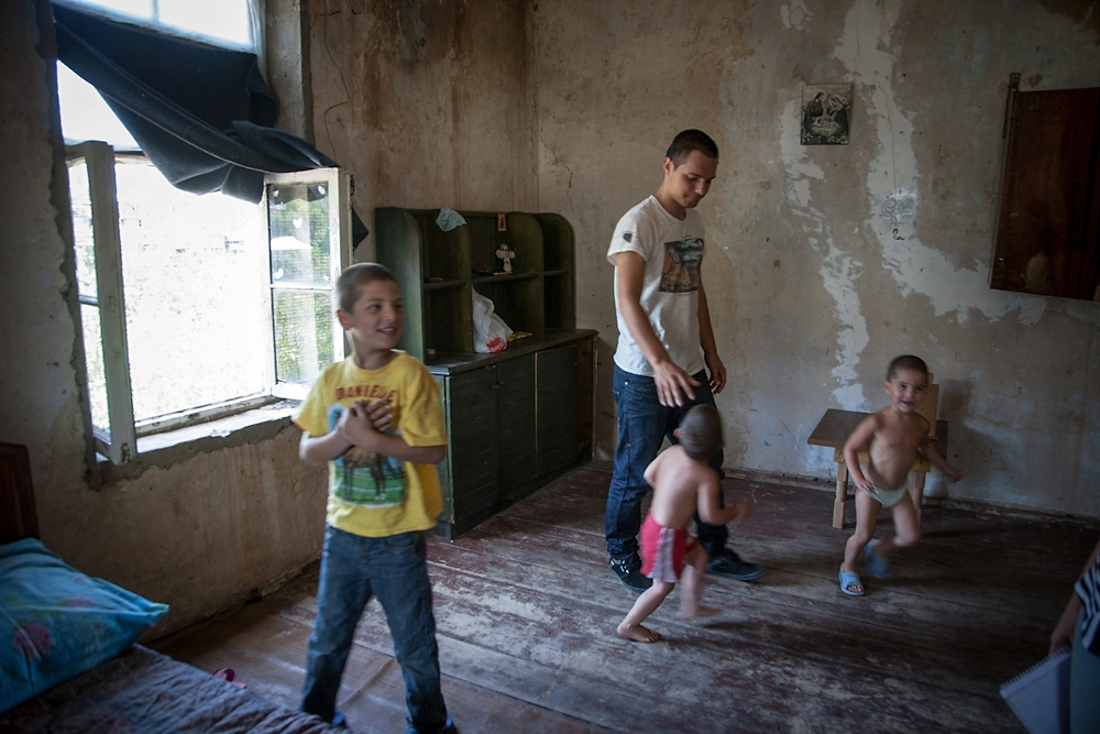 Former street child Anri Abashidze, who now works as a peer-educator, plays with kids in a house where one of his cases lives.