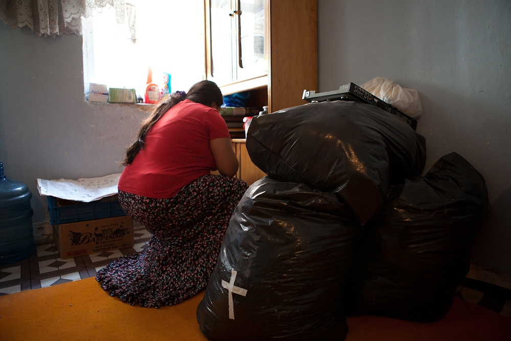 A family packs the last of their possessions into plastic garbage bags before leaving their apartment for good.