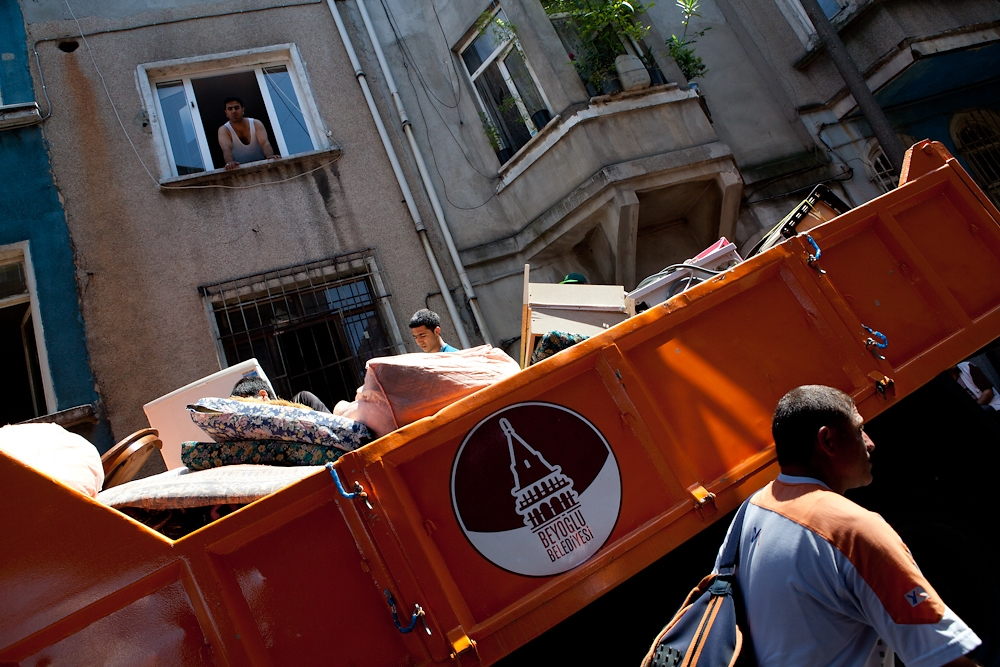 Municipality workers pack an open truck with the belongings from an evicted family.