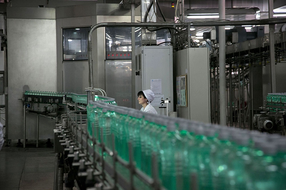 A worker monitors filled bottles for quality at Borjomi Bottling Factory #2.