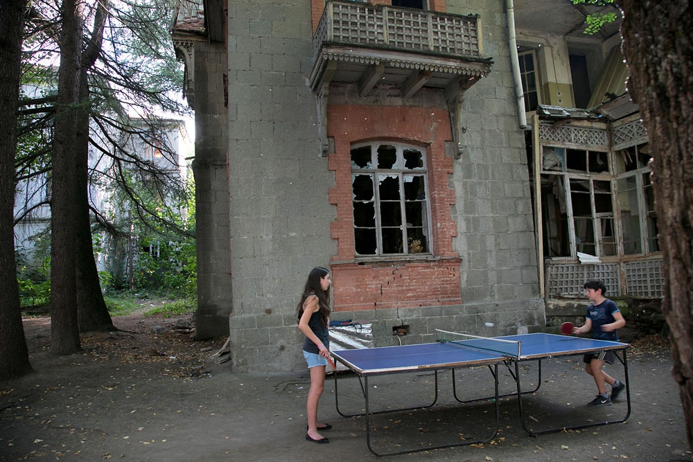 Children play table tennis outside a decaying former medical clinic in the center of Borjomi.