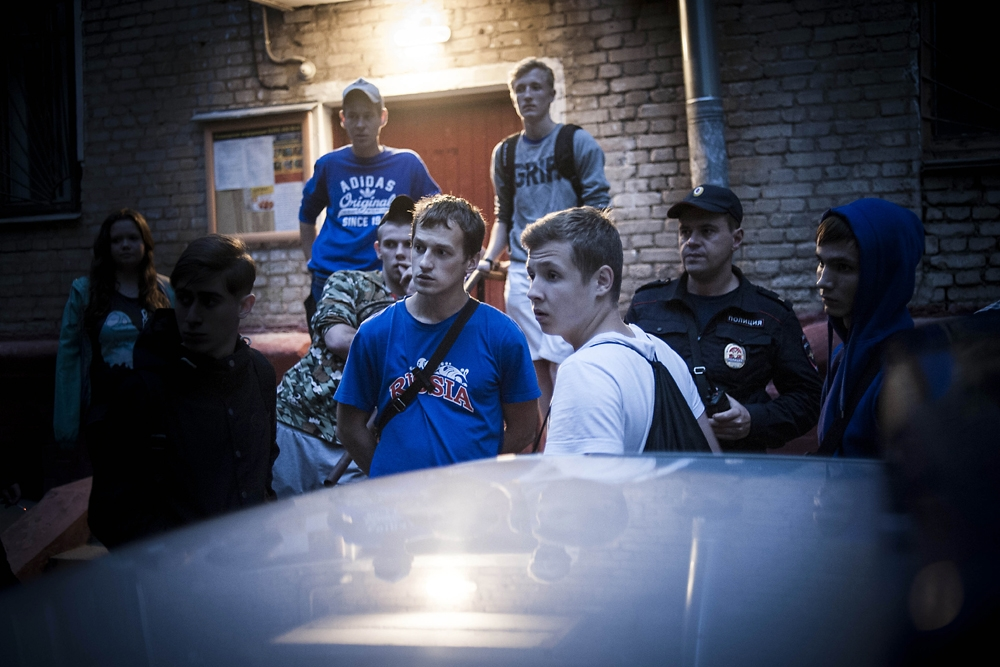 Members of Moscow Shield watch police gather Uzbek migrants, whom the organization found living illegally in a basement.